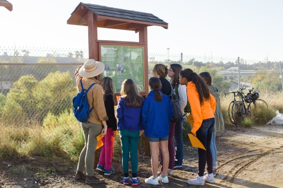Reading the interpretive sign. Photo by Rosten Woo.